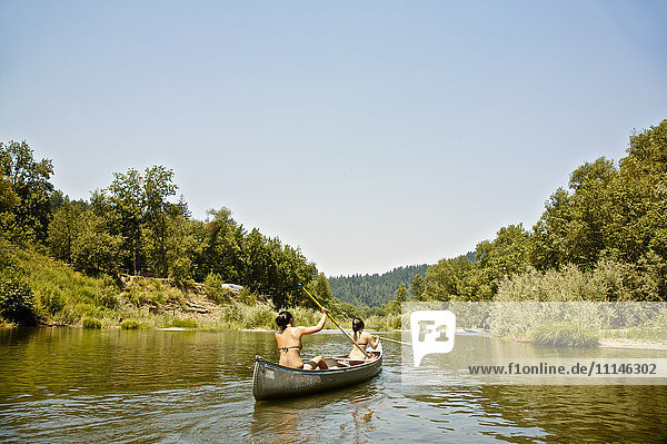 Rear view of women rowing canoe in rural lake