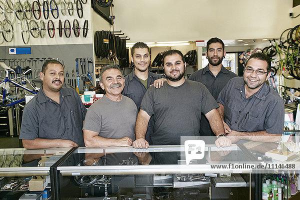 Mechanics smiling in bicycle repair shop