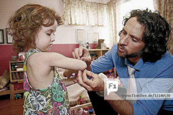 Caucasian father examining daughter's scrape