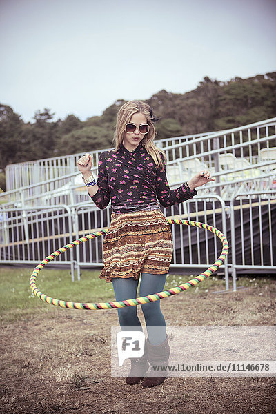 Woman playing with hula hoop at festival