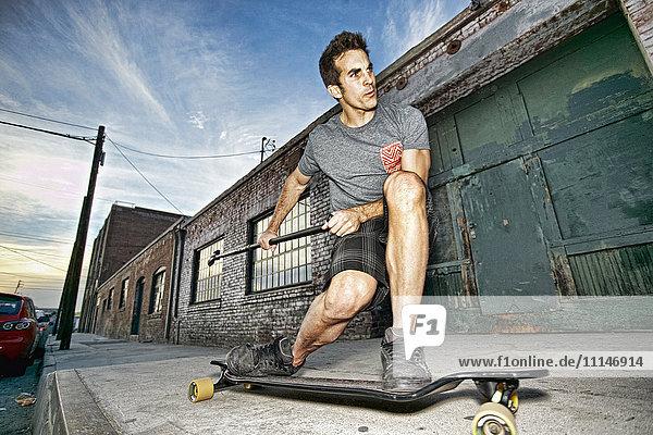Caucasian man riding skateboard with land paddle Caucasian man riding skateboard with land paddle
