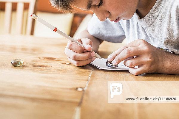 Mixed race boy coloring at desk Mixed race boy coloring at desk