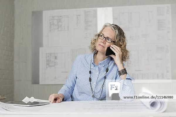 Caucasian architect talking on phone at desk