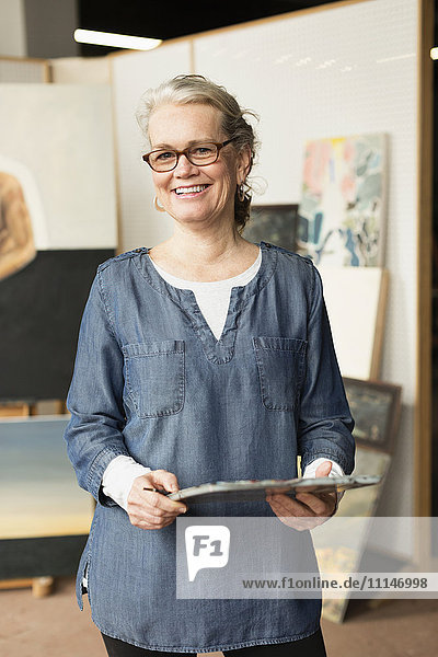 Caucasian artist smiling in studio