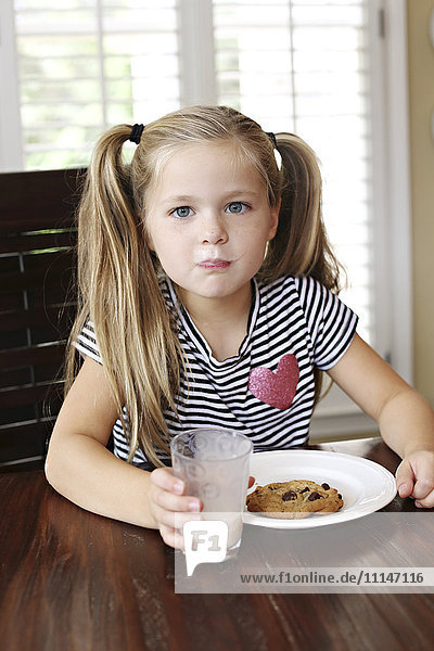 Girl eating cookies with milk mustache at table
