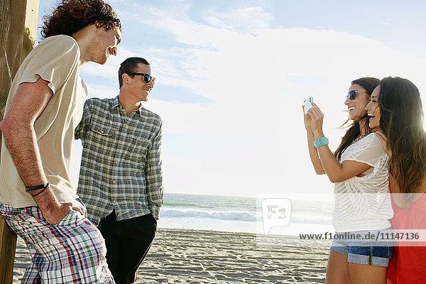 Women taking picture of boyfriends on beach