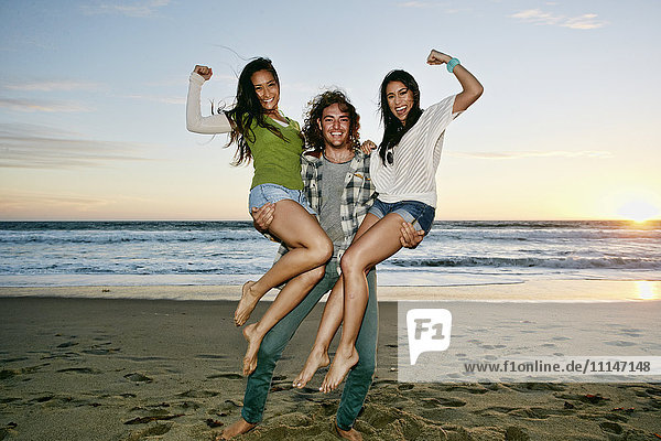 Man holding women on each arm on beach