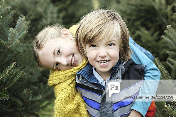 Siblings hugging near pine trees