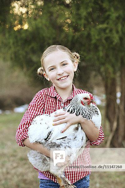 Caucasian girl holding chicken on farm