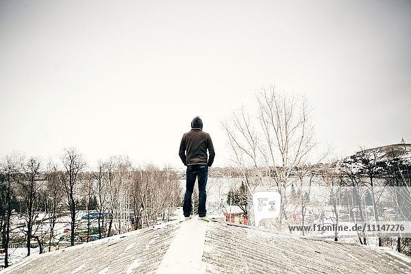 Caucasian man standing on snowy roof