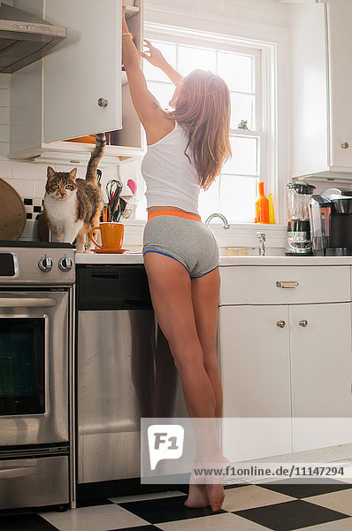 Mixed race woman wearing underwear in kitchen with cat