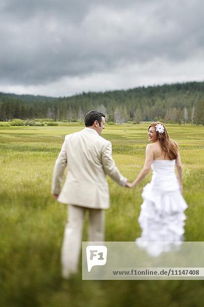 Caucasian bride and groom walking in rural field