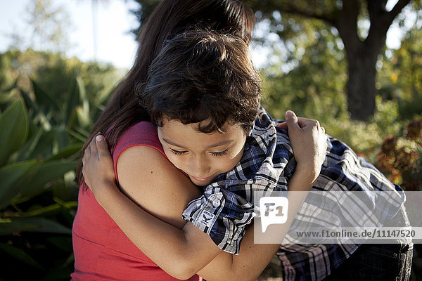 Mother and son hugging outdoors