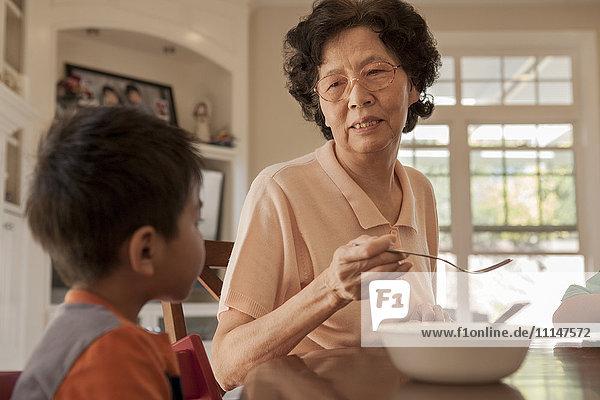 Asian grandmother feeding grandson at table