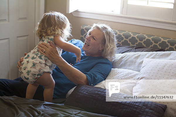 Grandmother and granddaughter playing on bed