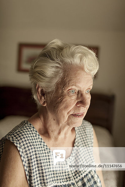 Pensive older woman sitting on bed