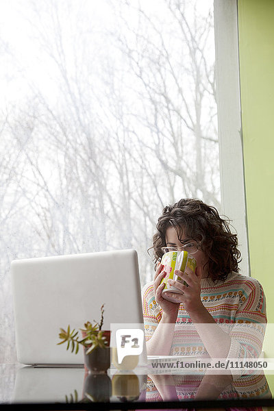Caucasian businesswoman drinking coffee at desk