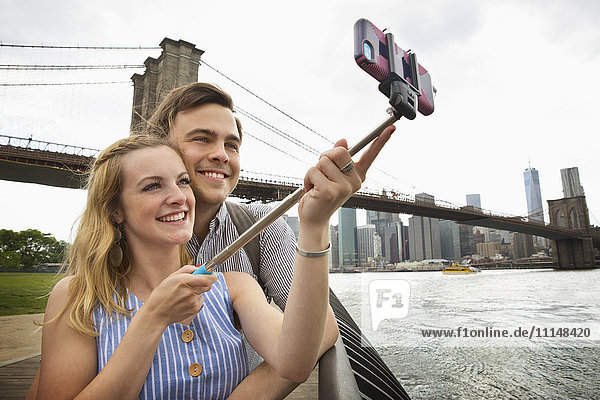 Caucasian couple taking selfie with cell phone under Brooklyn Bridge  Brooklyn  New York  United States