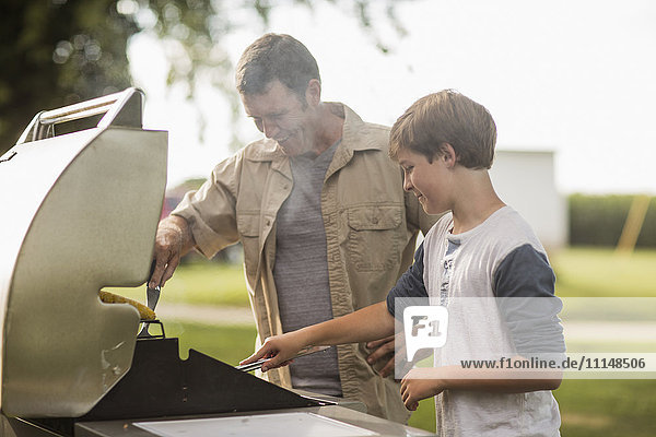 Caucasian father and son grilling food in backyard