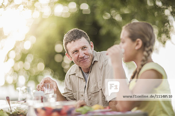 Caucasian father and daughter eating in backyard