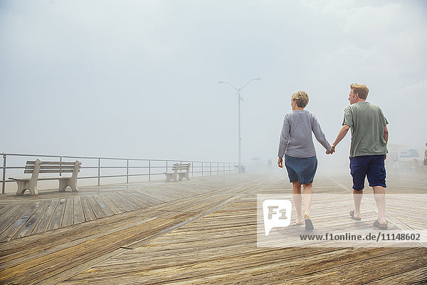 Couple holding hands on wooden boardwalk
