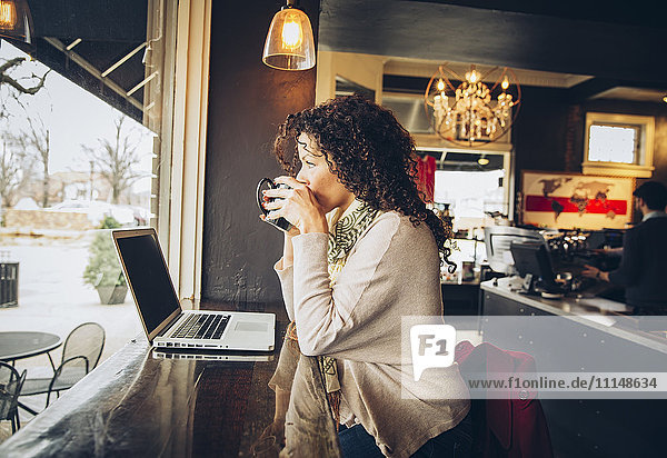 Woman using laptop and drinking coffee in cafe