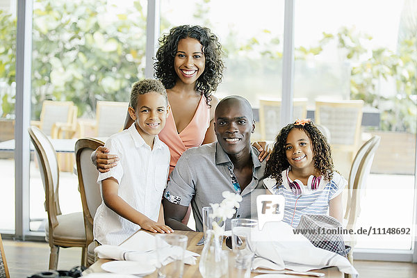 Family smiling at restaurant table