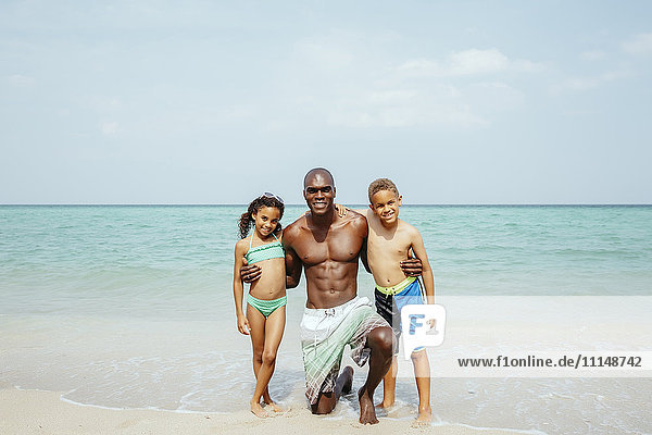 Father and children hugging on beach