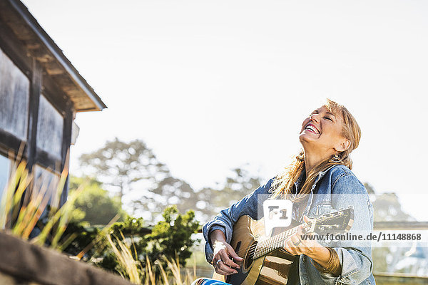 Caucasian woman playing guitar on porch Caucasian woman playing guitar on porch