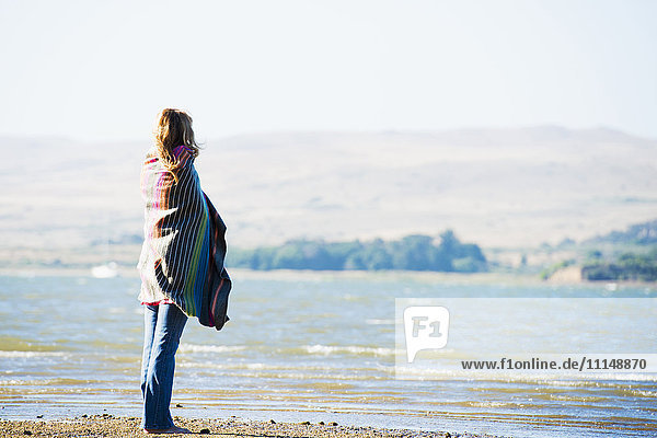 Caucasian woman wrapped in blanket on beach Caucasian woman wrapped in blanket on beach