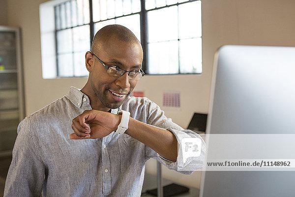 Mixed race businessman talking into smart watch in office