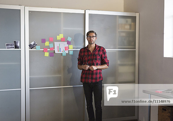 Caucasian businessman standing by cabinet in office