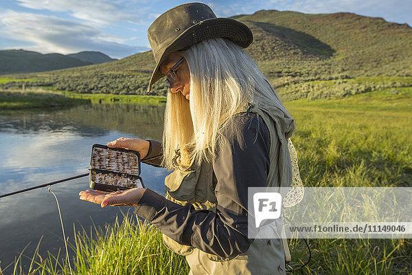 Caucasian woman examining fishing tackle near remote lake