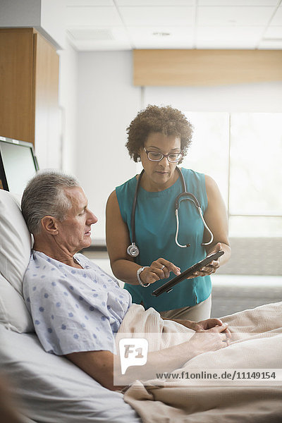 Doctor using digital tablet with patient