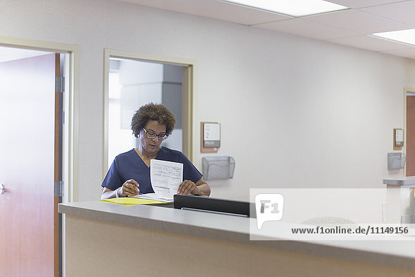 African American nurse writing in hospital