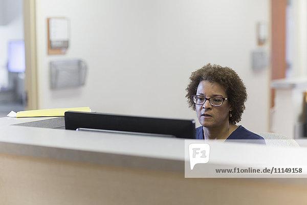 African American nurse using computer in hospital