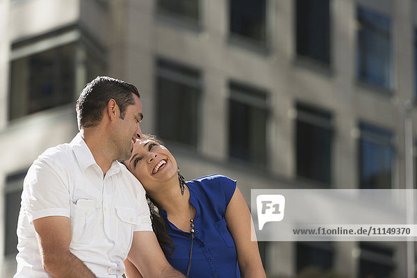 Hispanic couple hugging in city