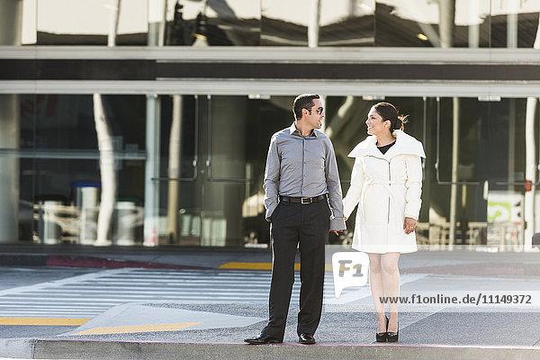 Hispanic couple holding hands on city sidewalk
