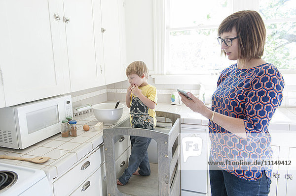 Mother and son standing in kitchen