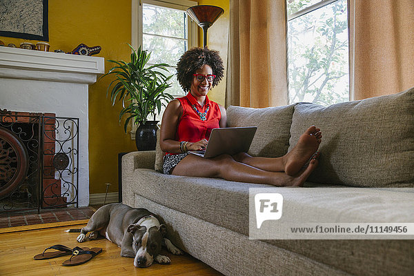 Mixed race woman using laptop on sofa