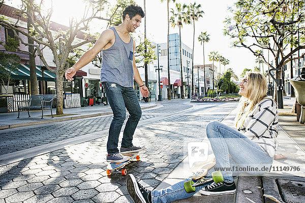 Caucasian couple riding skateboards