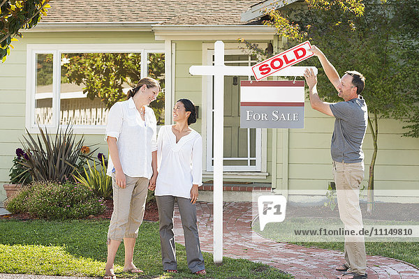 Real estate agent hanging sign outside house