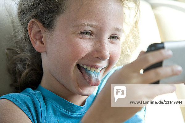 Caucasian girl with blue tongue taking selfie with cell phone