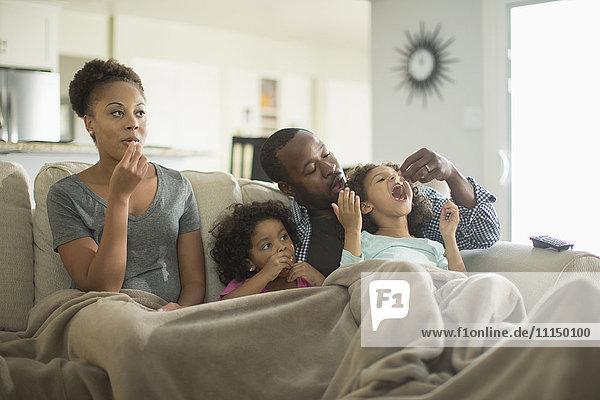 Family in blanket snacking on sofa
