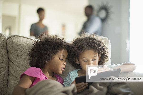 Sisters using digital tablet on sofa
