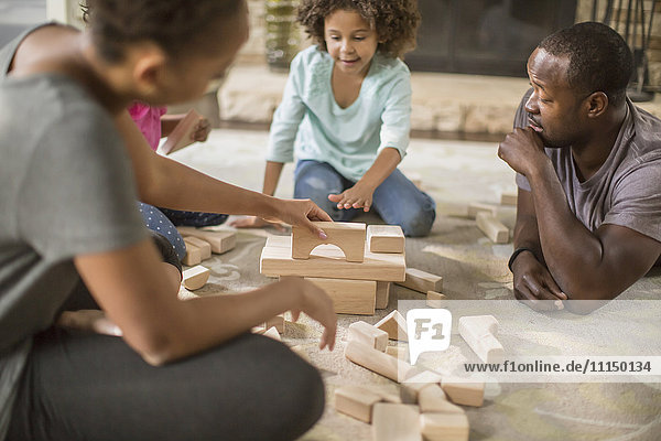 Family playing with building blocks in living room