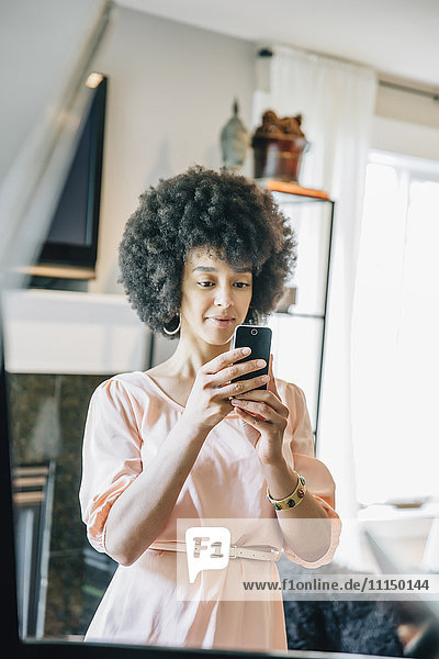Mixed race woman using cell phone in living room