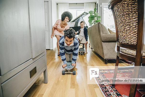Mixed race family watching boy ride skateboard in living room