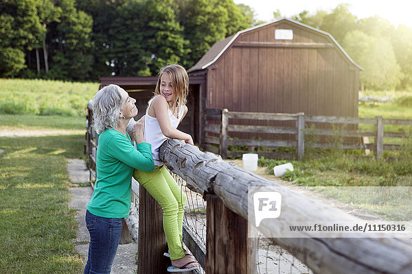 Caucasian grandmother and granddaughter smiling at farm fence
