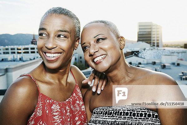 Black women smiling on urban rooftop